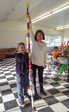 Girl standing with toy tower