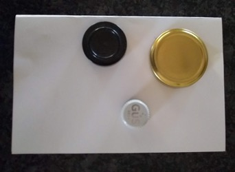 Different size lids sitting on paper