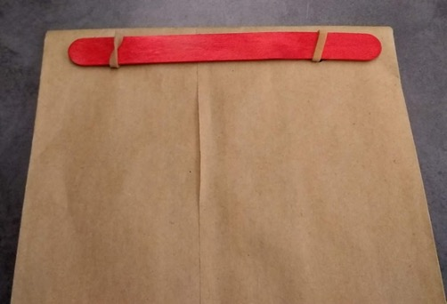 Stick held in place with rubber bands to the bag