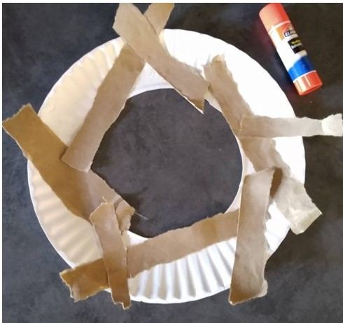 Glue the strips onto the paper plate